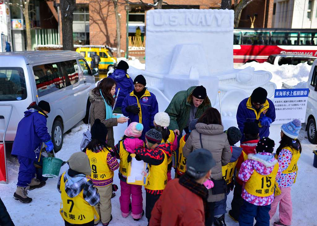 Members of the 2016 Sapporo Snow Festival Navy sculpting team interact with Japanese children. 2016's Navy themed sculpture is a 10 feet by 10 feet three-dimensional surface warfare pin.