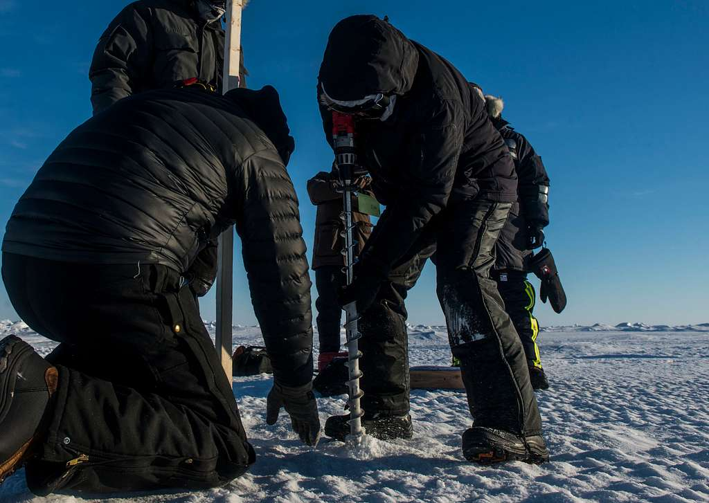 Dr. Joan Gardener, right, and Dr. Rick Hagen, with the Naval Research Laboratory, drill a hole into 6 feet of ice to collect water samples, ice cores, and temperature readings.