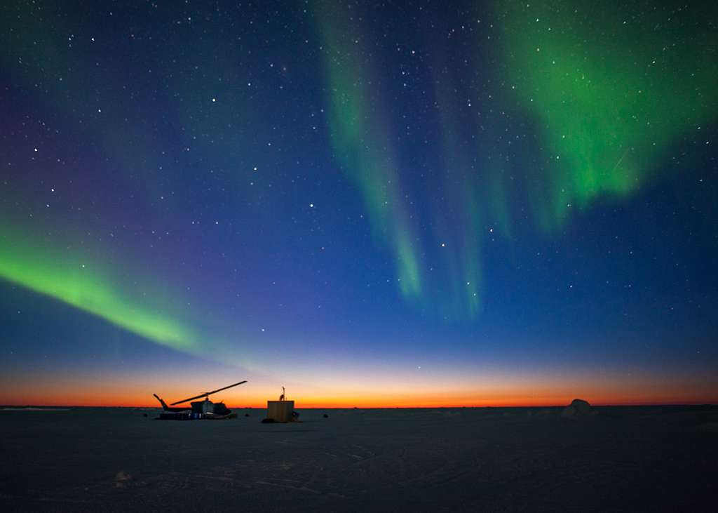 The aurora borealis appears over Ice Camp Sargo as the sun sets during Ice Exercise (ICEX) 2016.