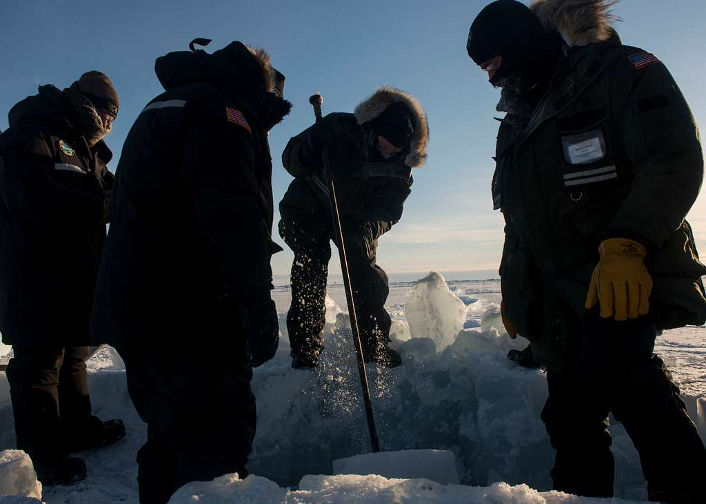 Sailors and civilians, assigned to Arctic Submarine Lab, clear the ice from the hatch of USS Hampton (SSN 767) during Ice Exercise (ICEX) 2016.