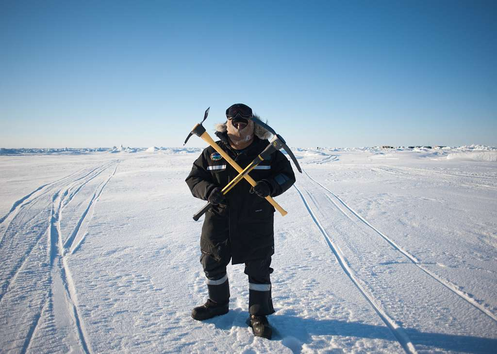 Hull Technician 2nd Class Joseph Deacon, assigned to Arctic Submarine Lab, hold up the Hull Technician rating symbol after mining for ice during Ice Exercise (ICEX) 2016.