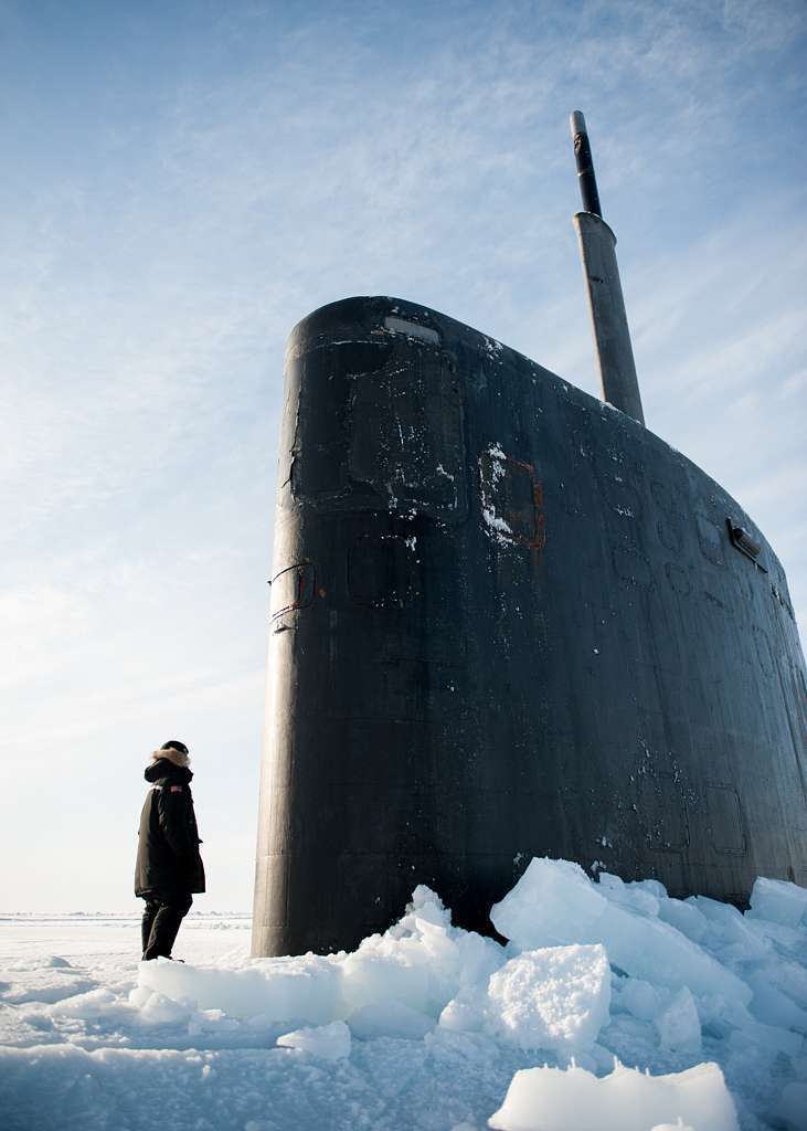 Mass Communication Specialist 2nd Class Tyler Thompson, assigned to Expeditionary Combat Camera, Stands in front of Los Angeles Class submarine USS Hampton (SSN 767) during Ice Exercise (ICEX) 2016.
