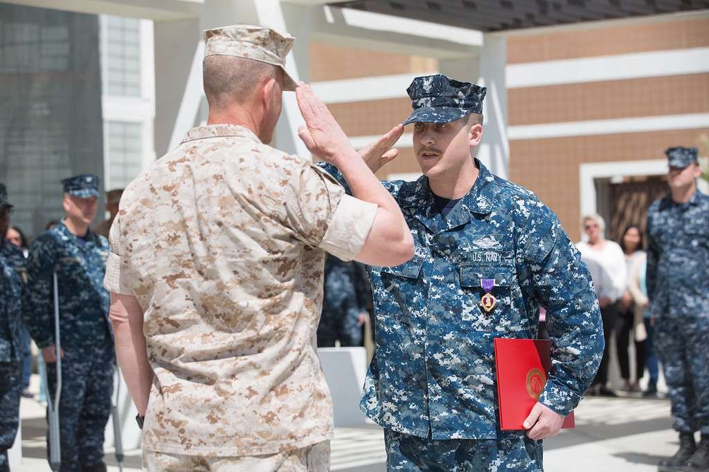 Petty Officer 2nd Class Joshua Bellavia, corpsman, Adult Medical Care Clinic, salutes Maj. Gen. Lewis A. Craparotta, Combat Center Commanding General, during Bellavia's Purple Heart Medal presentation ceremony at Robert E. Bush Naval Hospital.