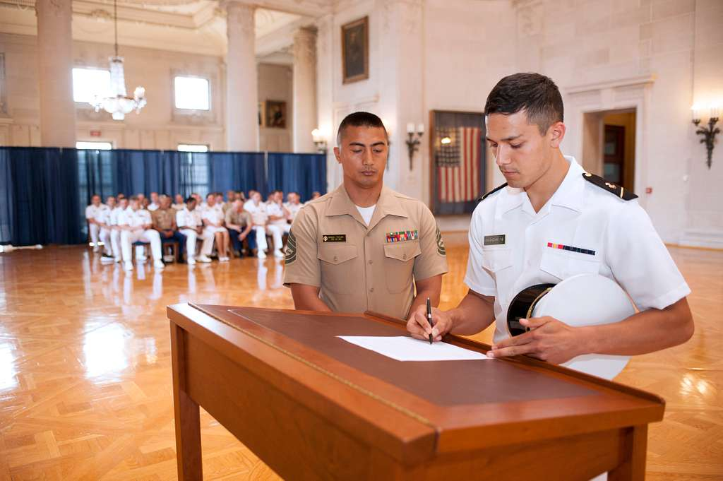 The third class midshipmen Daniel Iskandar signs his 2 for 7 commitment contract in Memorial Hall at the U.S. Naval Academy.