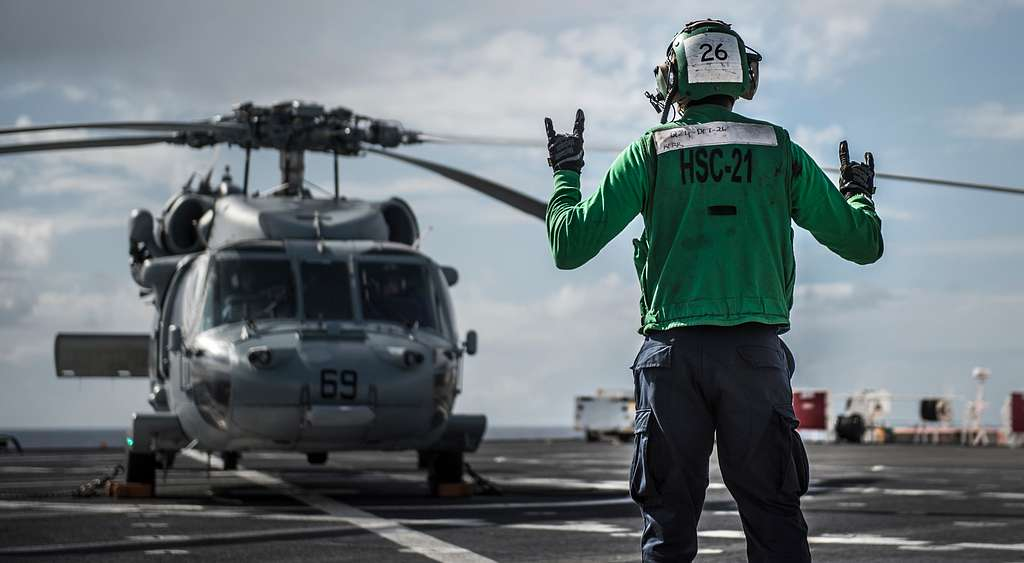 Aviation Electronics Technician 3rd Class Daniel Kerr, a native of Montego Bay, Jamaica, signals  a MH-60S assigned to the Blackjacks of Helicopter Sea Combat Squadron (HSC) 21 during preflight checks aboard hospital ship USNS Mercy (T-AH 19).