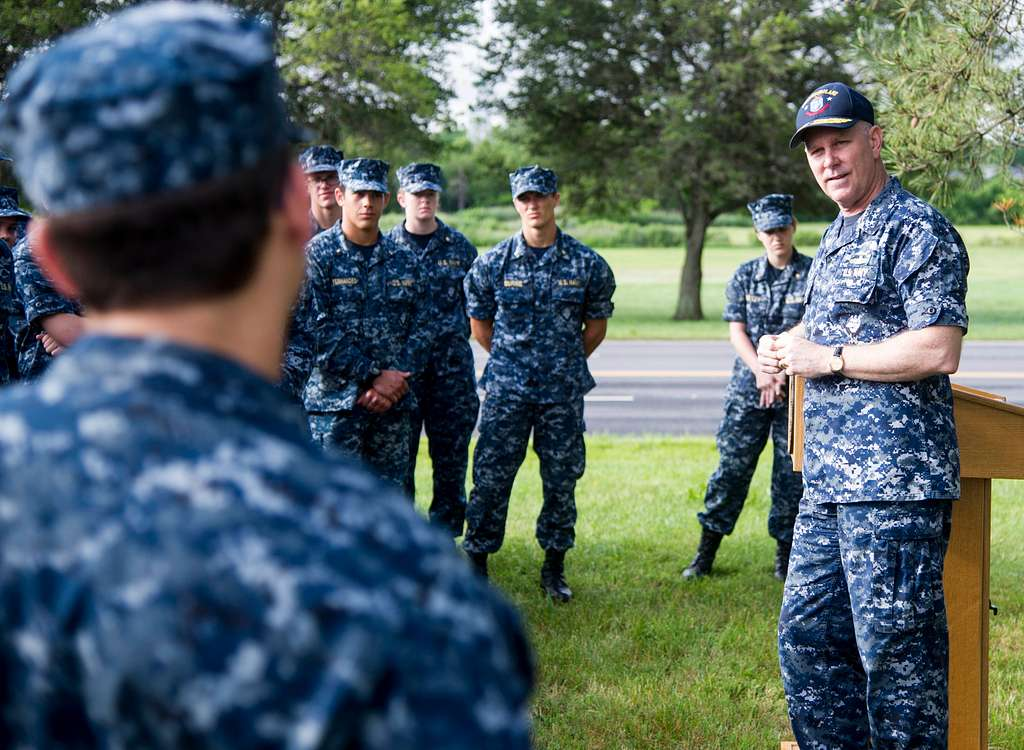 Rear Adm. Christopher Grady, Commander, Naval Surface Force Atlantic, right, speaks with midshipmen at the USS Cole Memorial aboard Naval Station Norfolk.