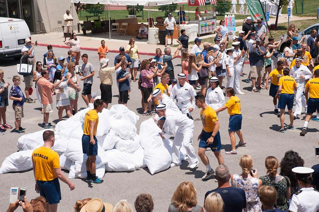 Incoming plebes from the U.S. Naval Academy's (USNA) class of 2020 grab laundry bags from the parking lot of the Midshipmen store during induction day (I-day) 2016.