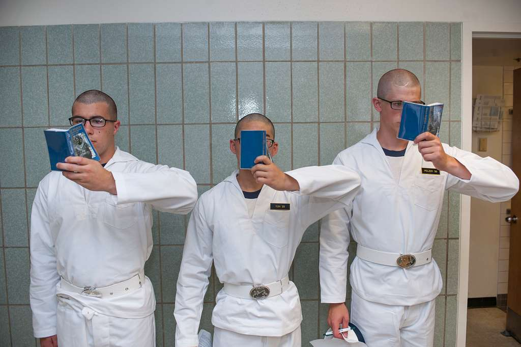 Plebes from the U.S. Naval Academy (USNA) stand against a wall in Bancroft Hall reading their