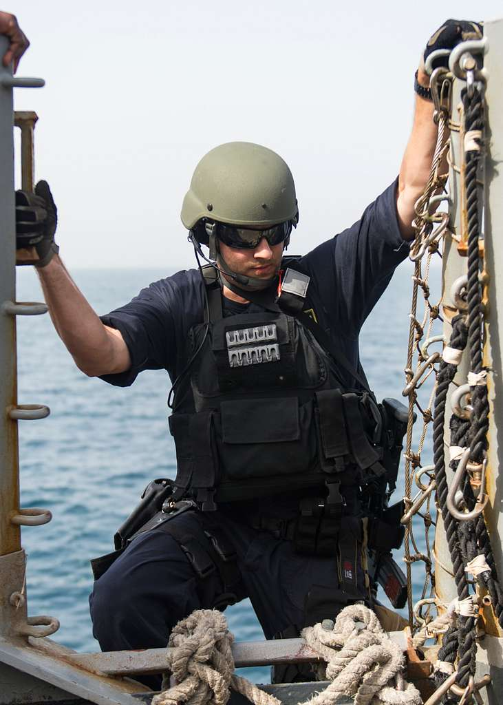 Fire Controlman 2nd Class Tyler Moore climbs down a pilot's ladder into a rigid hull inflatable boat from aboard USS Stout (DDG 55) during a visit, board, search and seizure (VBSS) exercise.