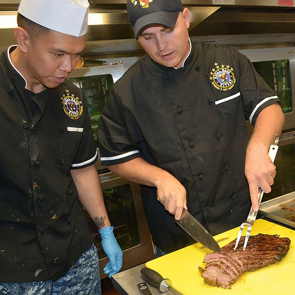 Naval Base Kitsap (NBK) Culinary Specialist (CS) Chief Jonathon Miller (right) displays optimal flank steak cutting techniques to CS2 Mac Fernandez.