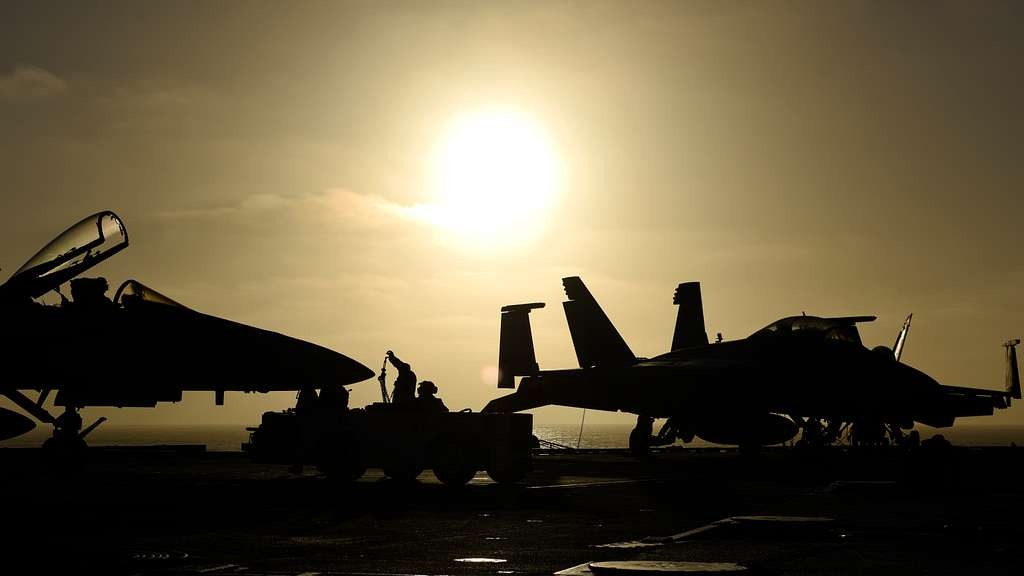 Sailors assigned to the aircraft carrier USS Nimitz (CVN 68) chock and chain aircraft on the flight deck.