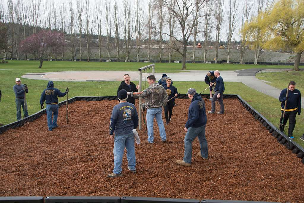 Sailors assigned to Patrol Squadron (VP) 40 spread wood chips onto a playground during a community relations event at Windjammer Park in Oak Harbor, Wash.
