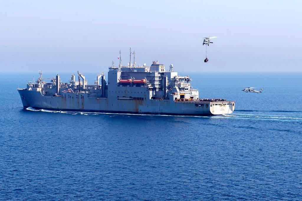 An MH-60S Sea Hawk helicopter assigned to the Eightballers of Helicopter Sea Combat Squadron (HSC) 8 transports supplies from the dry cargo ship USNS Carl Brashear (T-AKE7) .