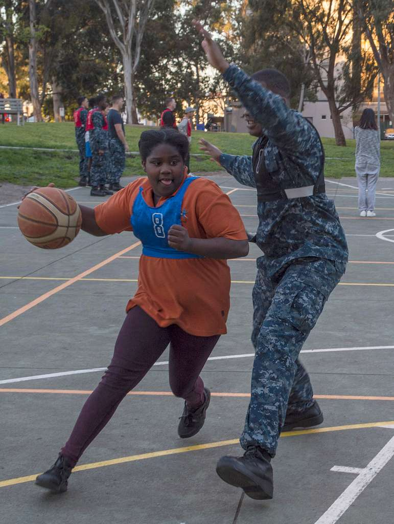 Aviation Boatswain's Mate (Handling) Airman Jalon Wilson plays basketball with a child during a community relations event at the Helping Hoops Richmond Basketball Clinic.