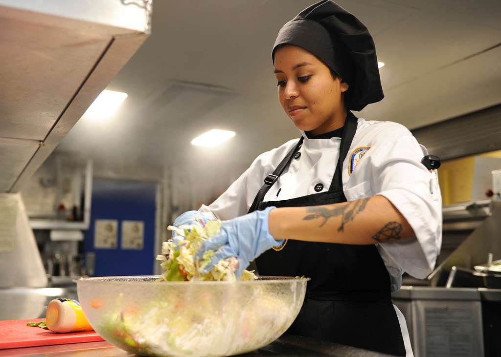 Culinary Specialist Seaman Michelle Martinez prepares coleslaw in the galley aboard the amphibious assault ship USS Boxer (LHD 4).
