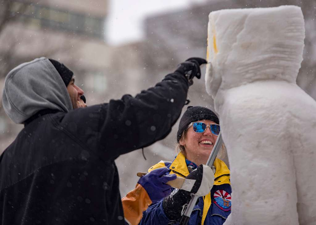Logistics Specialist 3rd Class Christopher Hamilos, left, and Aviation Support Equipment Technician 2nd Class Leah Alstad, detail the 2018 Navy Snow Team Sculpture for the 69th Annual Sapporo Snow Festival.