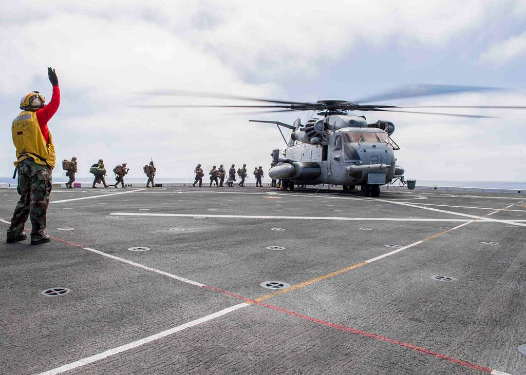 Aviation Boatswain's Mate (Handling) 1st Class Della Smith signals Marines assigned to 13th Marine Expeditionary Unit (13th MEU) to board a CH-53E Super Stallion helicopter assigned to Marine Medium Tiltrotor Squadron (VMM) 166.