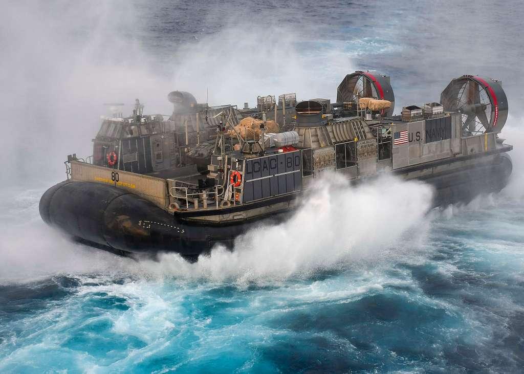 A landing craft, air cushion (LCAC) attached to Assault Craft unit (ACU) 5, travels behind the Wasp-class amphibious assault ship USS Essex (LHD 2)
