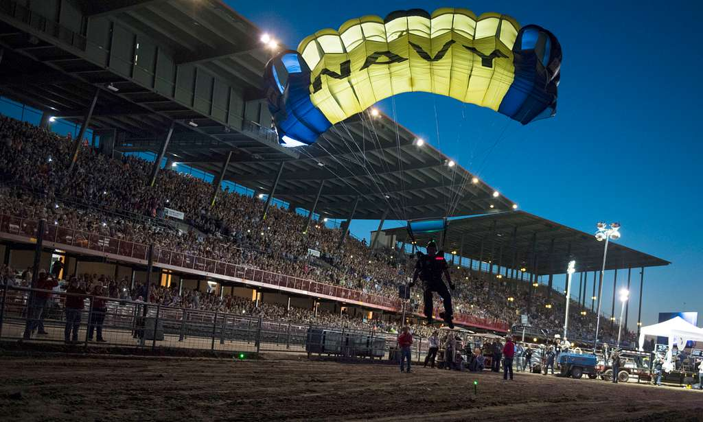 A member of the U.S. Navy parachute team, The Leapfrogs, prepares to land into the opening ceremonies of a professional bull riding competition at the 2018 Cheyenne Frontier Days.
